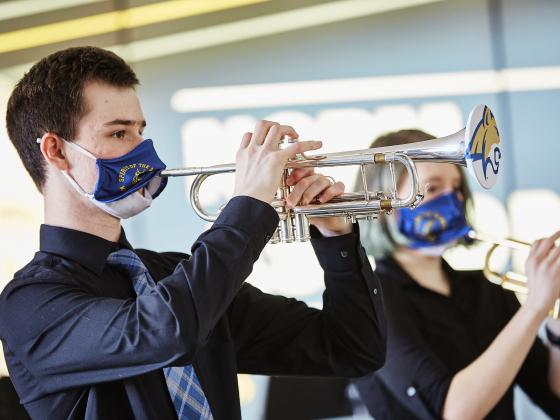 A man in a black shirt plays a trumpet through a face mask. | MSU Photo by Adrian Sanchez-Gonzalez
