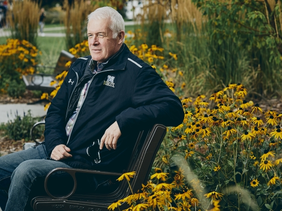 A man sits on a bench posing for a portrait with yellow flowers in the background. | MSU Photo by Adrian Sanchez-Gonzalez