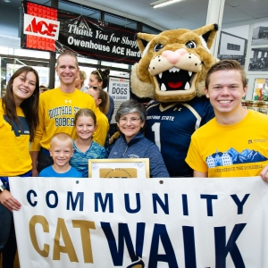 Photo of students, Champ and President Cruzado holding a Community Cat Walk banner