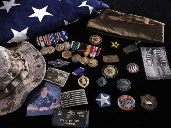 Still life photo of an American flag and military patches and medals. | MSU photo by Kelly Gorham