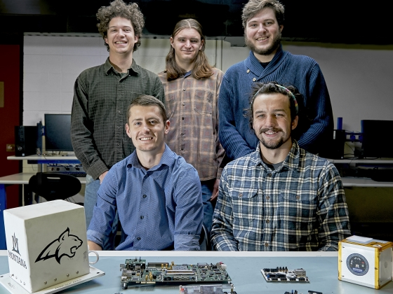 Photo of a group of three standing and two seated engineering students with satellite components on a table in the foreground. | MSU photo by Kelly Gorham