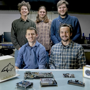 Photo of a group of three standing and two seated engineering students with satellite components on a table in the foreground.