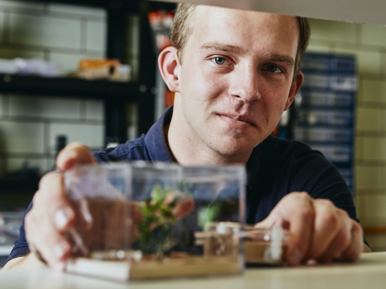 A man poses for a portrait behind a glass container inside a lab. | MSU Photo by Adrian Sanchez-Gonzalez