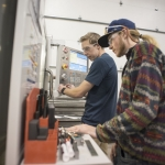 Kyle Stinson, left, and Duncan McIntosh monitor the milling process in a CNC machine. MSU photo by Kelly Gorham