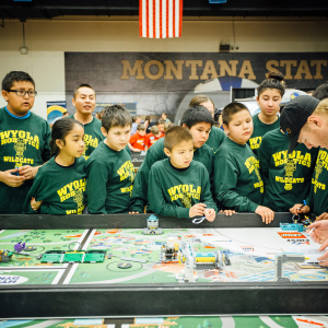 a team wearing green shirts gathers around a table with a robotics course, intently focused.