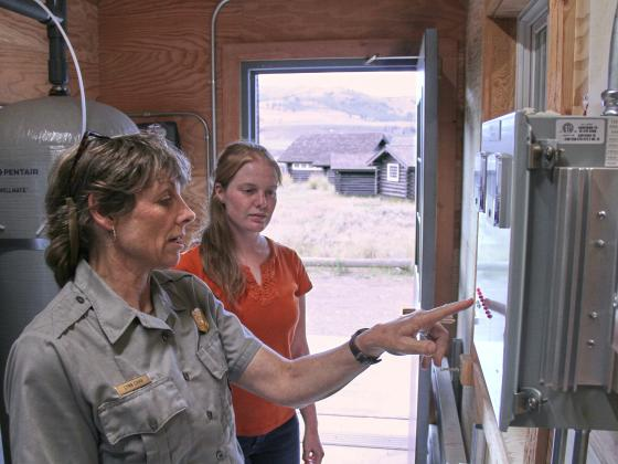A woman Park Service official at left points to an electronic box while consulting with MSU student in orange shirt with cabin visible beyond open door |