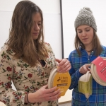 Montana State University graphic design students Sarah Tuma, left, and Gabrielle Lewis examine their projects before a presentation Monday, Dec. 12, 2016. Teams  of graphic design, nutrition and business students worked with local food producers to create marketable retail products. MSU photo by Kelly Gorham.