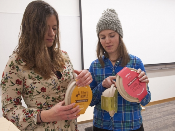 Montana State University graphic design students Sarah Tuma, left, and Gabrielle Lewis examine their projects before a presentation.