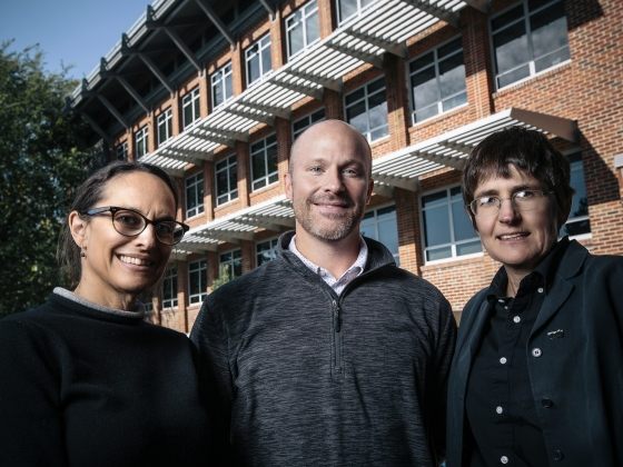 Three professors pose for a group photo in front a modern laboratory building. | MSU Photo by Adrian Sanchez-Gonzalez