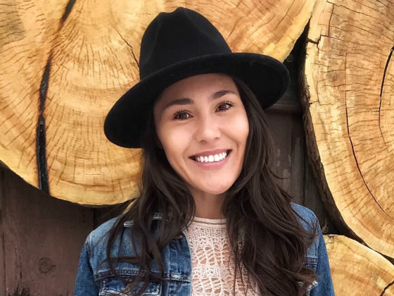 Photo of a smiling woman with long dark hair in a black hat and jean jacket in front of large log slices. |