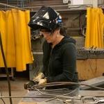 A woman in welding gear cutting metal.