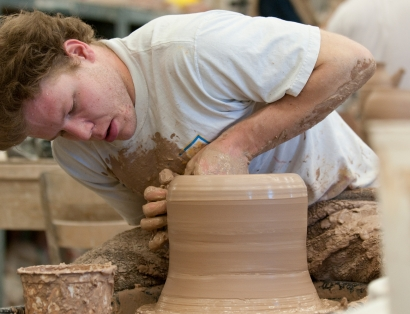 A student creates a clay sculpture