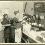 Vintage photo of two World War I soldiers feed fellow soldiers who line up for food.