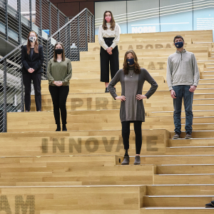 Eight students wearing masks and spaced apart from one another stand on a large staircase.