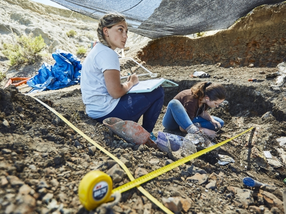 A woman sits on a dirt bed surrounded by measuring tape at an excavation site. | MSU Photo by Adrian Sanchez-Gonzalez