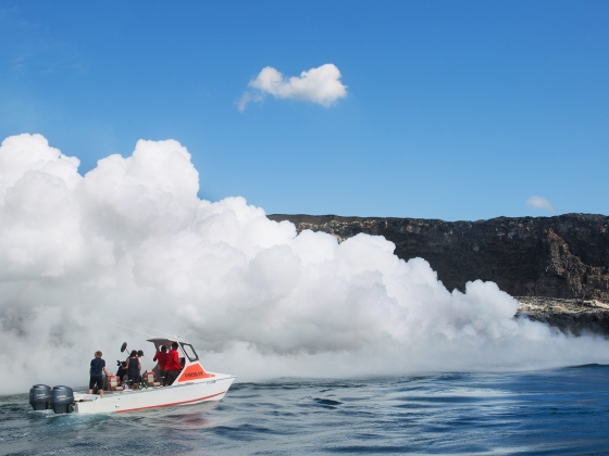 A boat near a volcanic steam cloud rising from a nearby shoreline.  | Courtesy of the 'The Most Unknown'