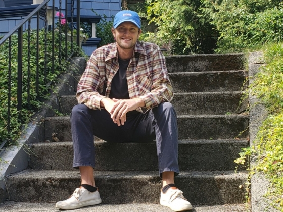 A man in a plaid shirt and blue hat sits on some steps outdoors | Photo Courtesy of McKay Reed