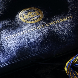 A Montana State University diploma cover and tassle
