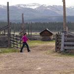 A women closes a gate on a ranch with mountains in the background.