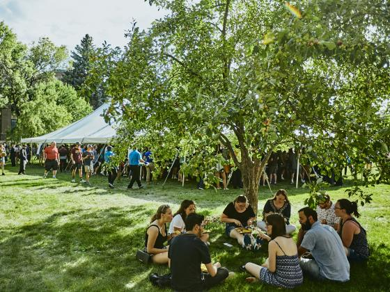 Group of students sitting in the grass while they eat at an outdoor barbecue event.    MSU photo by Adrian Sanchez-Gonzalez