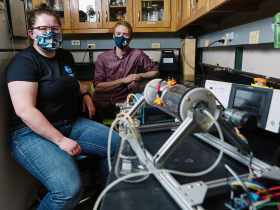 A woman in a black t-shirt and face mask and a man in a magenta shirt and face mask pose for a portrait inside a lab with a device in the foreground. | MSU Photo by Adrian Sanchez-Gonzalez