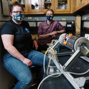 A woman in a black t-shirt and face mask and a man in a magenta shirt and face mask pose for a portrait inside a lab with a device in the foreground.