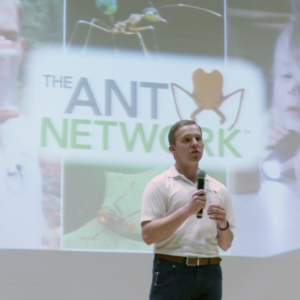 Man standing in front of projected image of the Ant Network logo.