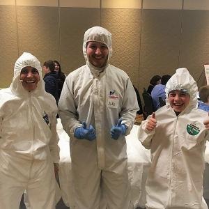 Three people try on Tyvex clean room suits.