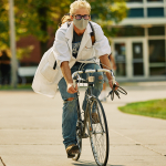 A man in a lab coat and face mask rides a bicycle on a paved path while wearing jeans.