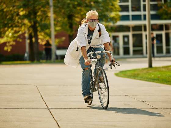 A man in a lab coat and face mask rides a bicycle on a paved path while wearing jeans. | MSU Photo by Adrian Sanchez-Gonzalez