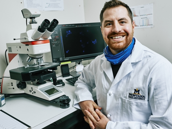 A man in a white lab coat poses for a portrait next to a microscope and computer.   ©2020 Montana State University, all rights reserved