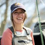 A woman wears a hat with a Trout U logo while sitting on a truck tailgate with fishing equipment.