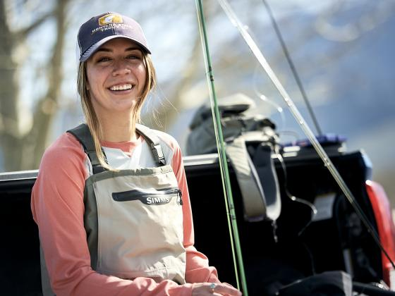 A woman wears a hat with a Trout U logo while sitting on a truck tailgate with fishing equipment. | MSU photo by Kelly Gorham