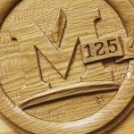 Detail of the MSU emblem carved on a wooden time capsule