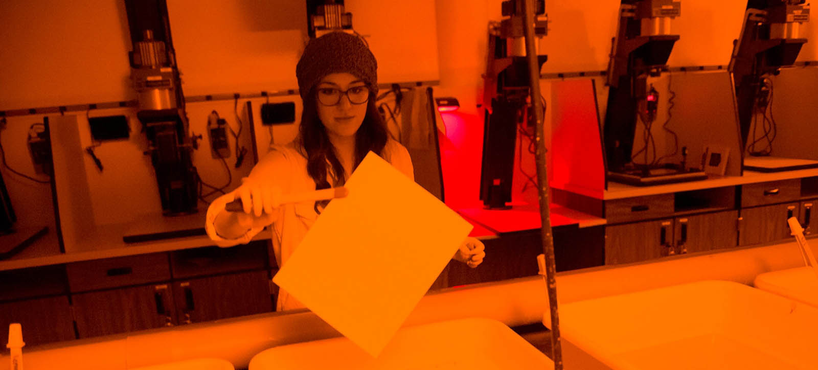 An MSU Photography student develops photographs in a darkroom.