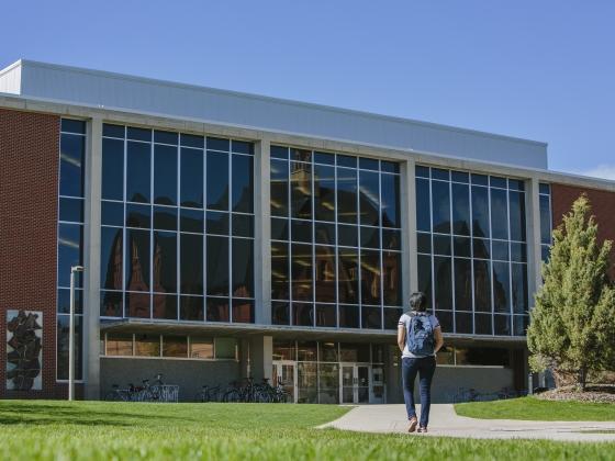 Photo of a person walking toward the MSU library building. | MSU photo by Adrian Sanchez-Gonzalez