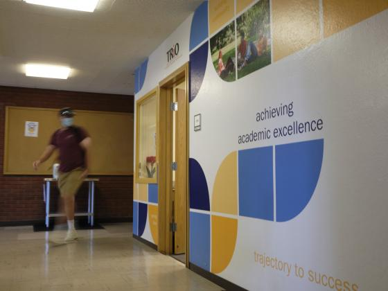 A photo of a person, motion-blurred, walking past an office with bright graphics on the walls. |