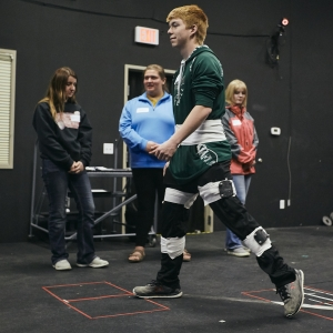 A student walks through a motion research lab as other students observe