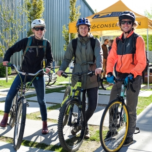 Three bike commuters stand with their bikes on a sunny morning during the May 2017 Commuter Challenge