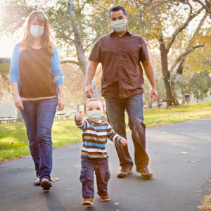Image of a family taking a walk with masks on