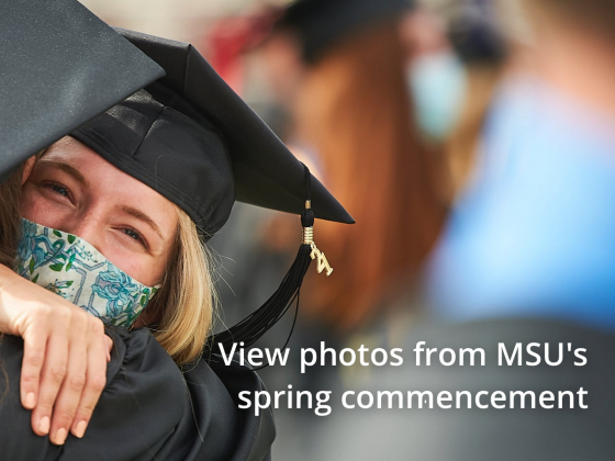 Two women in graduation gowns hug at a ceremony. | Kelly Gorham/MSU