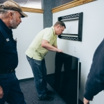 Jonathan Hilmer helps facilities crews install television screens for the CyberCANOE system in the Renne Library atrium at Montana State University, Friday, Jan. 6, 2017, in Bozeman, Mont. CyberCANOE is a data visualization and collaboration platform. MSU photo by Adrian Sanchez-Gonzalez