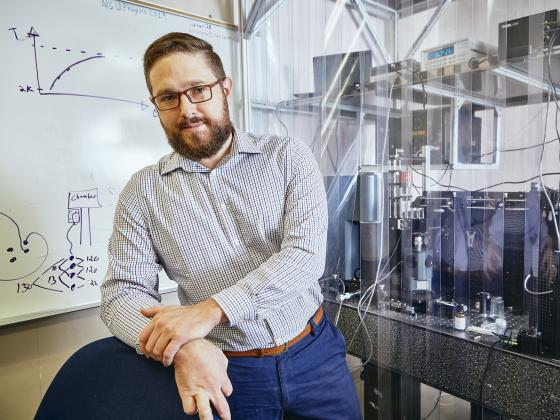 A bearded man in glasses stands in front of a whiteboard and a table of lab equipment. | MSU photo by Adrian Sanchez-Gonzalez