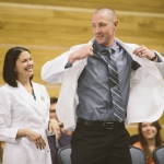 Brad Huff, one of the 30 students in the MSU WWAMI Medical Education Program, receives his white coat from Dr. Anne Rich, formally inducting him into the program during a white coat ceremony in the Strand Union Building on campus, Friday, Sept. 2, 2016, in Bozeman, Mont. MSU photo by Adrian Sanchez-Gonzalez
