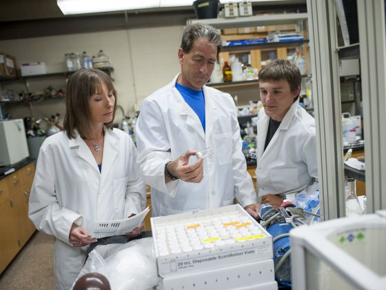 Montana State University professor and polar ecologist John Priscu, center, inspects samples from subglacial Antarctica in his lab in Bozeman, Mont., with graduate students Trista Vick-Majors, left, and Alex Michaud. MSU photo by Kelly Gorham