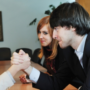 People in office attire are arm-wrestling