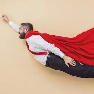 Man in office attire and superhero cape