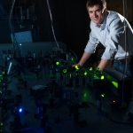 Erik Grumstrup, recipient of a U.S. Department of Energy early career award, is pictured in his laboratory at Montana State University in Bozeman. The double-exposed photo reveals light emitted by a laser, used for testing solar cell materials. (MSU photo illustration by Kelly Gorham).