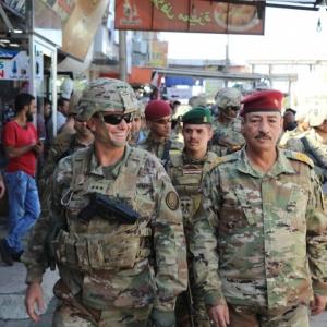 U.S Army Lt. Gen. Paul E. Funk II (Left), commanding general of Combined Joint Task Force-Operation Inherent Resolve, and Iraqi Maj. Gen. Najm Abdullah al-Jibouri (Right), commander of Nineveh Liberation Operation, walk through a busy market near the Univ
