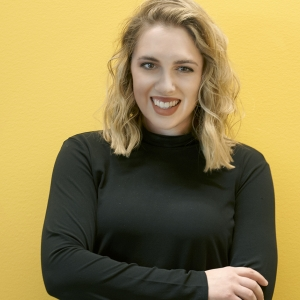 Photo of woman posing against a bright yellow wall.
